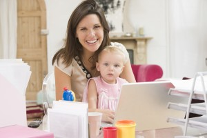 Mother and baby in home office with laptop